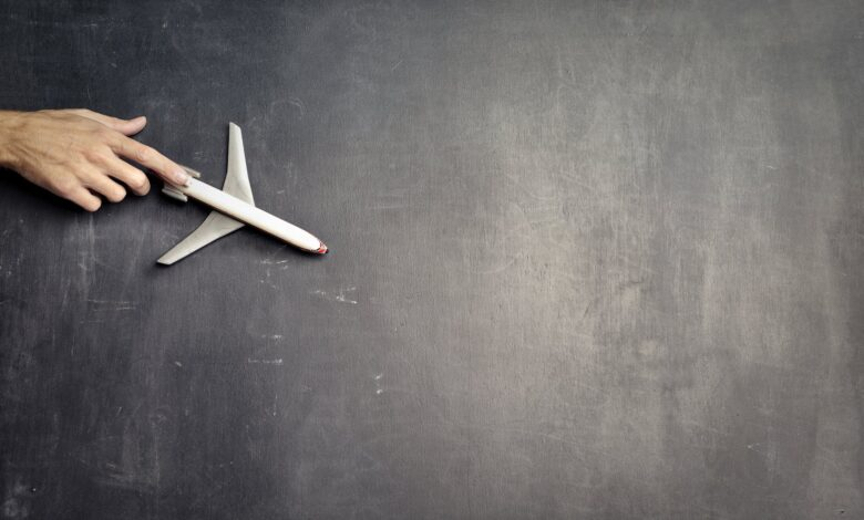 anonymous person with miniature airplane on chalkboard