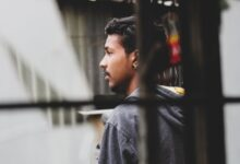 young ethnic man standing outside window on street